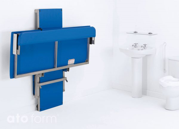 Hi-Riser Wickeltisch kann bei Nichtgebrauch platzsparend an die Wand hochgeklappt werden.